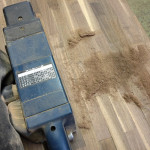 ウォルナットの表面の凹凸をベルトサンダーで研磨する