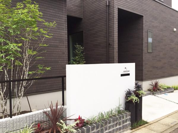 白い漆喰塀と植物がシンプルでモダンな印象の外構