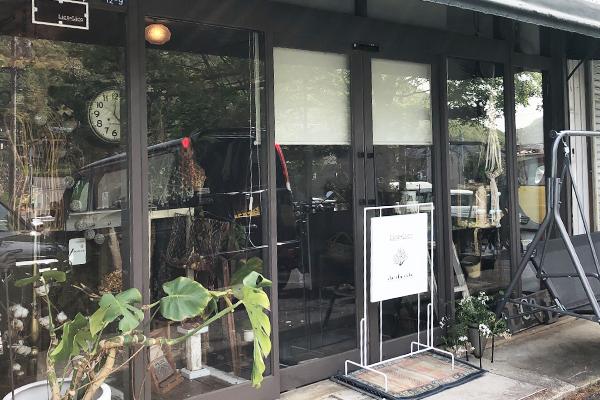 黒基調の店舗入り口に置かれた白いアイアン看板